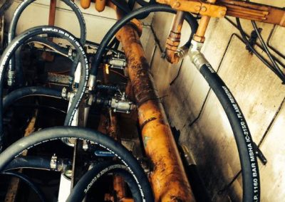 Mid-process, changing leaking / cracked passed their working life 1-inch hoses in a hydraulic pump room. For a large protein Recovery business.