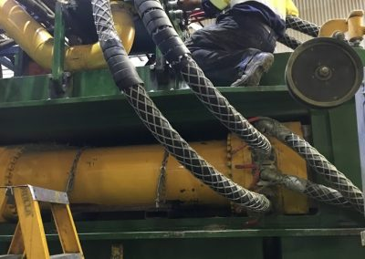 Mid-process of over 6, 2-inch multi-spiral hose with whip socks and spiral guard for safety on an aggressive manufacturing machine. For a large hay exporting company.